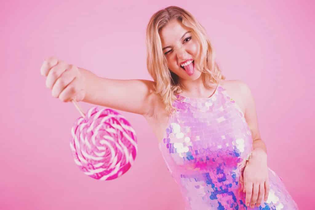 musician portrait of girl on pink background with lollipop