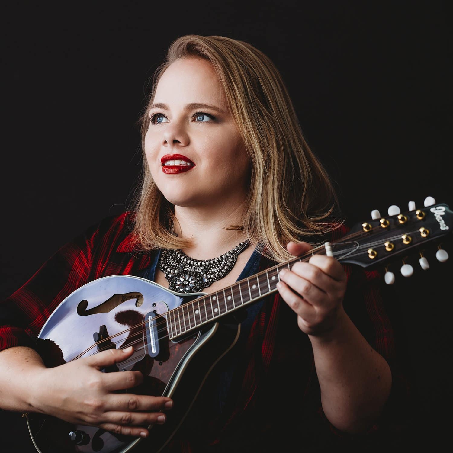 Claire Lipaulo wearing flannel and playing mandolin for personal brand