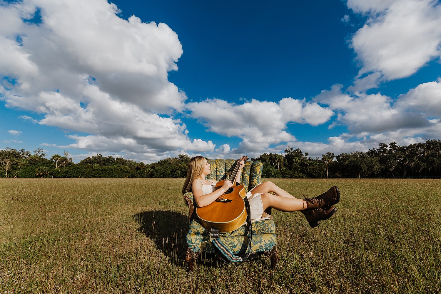 musician playing guitar in a field with big sky in Fort Myers, FL