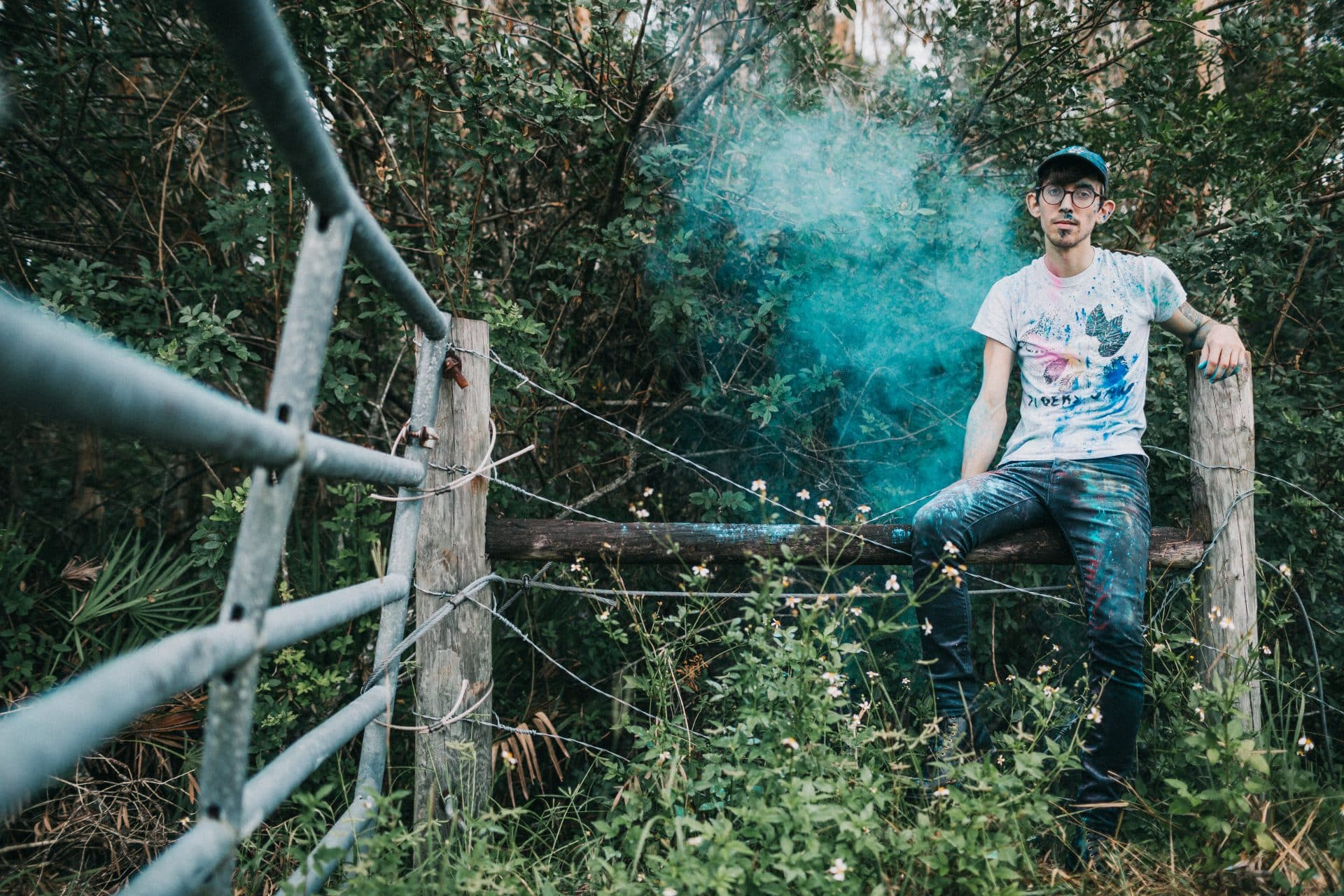man on a fence in the woods with blue smoke