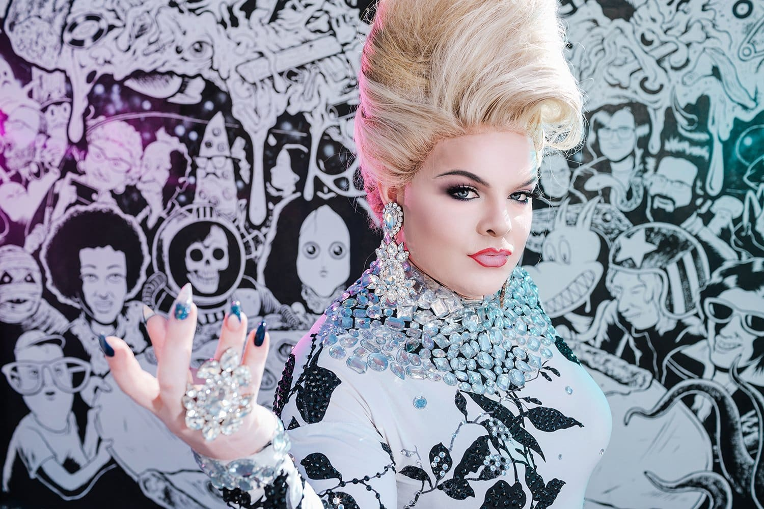 portrait photography drag queen wearing black and white dress and beehive hair on black and white mural background