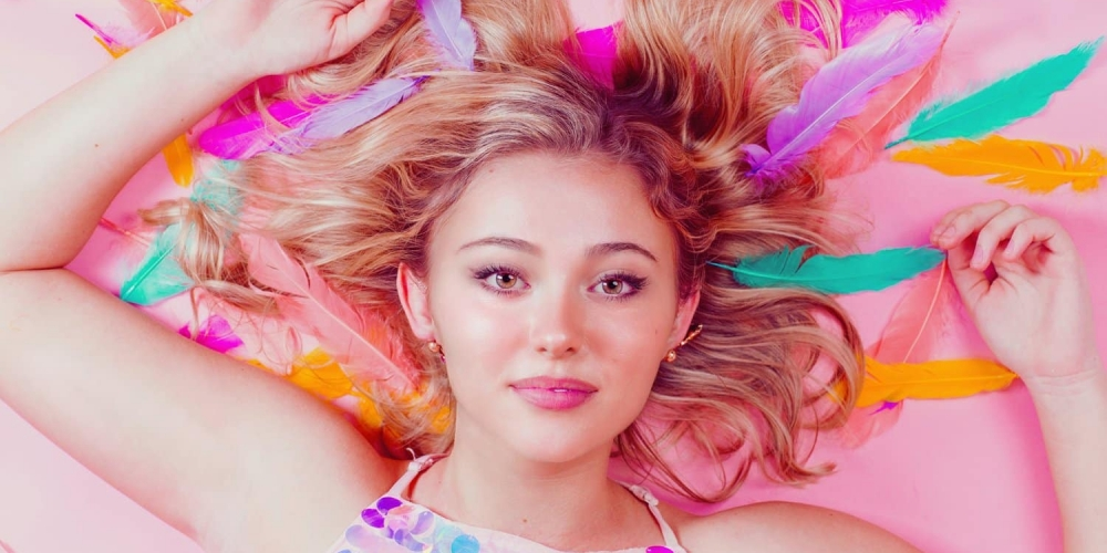 girl laying on pink background with bright colored feathers