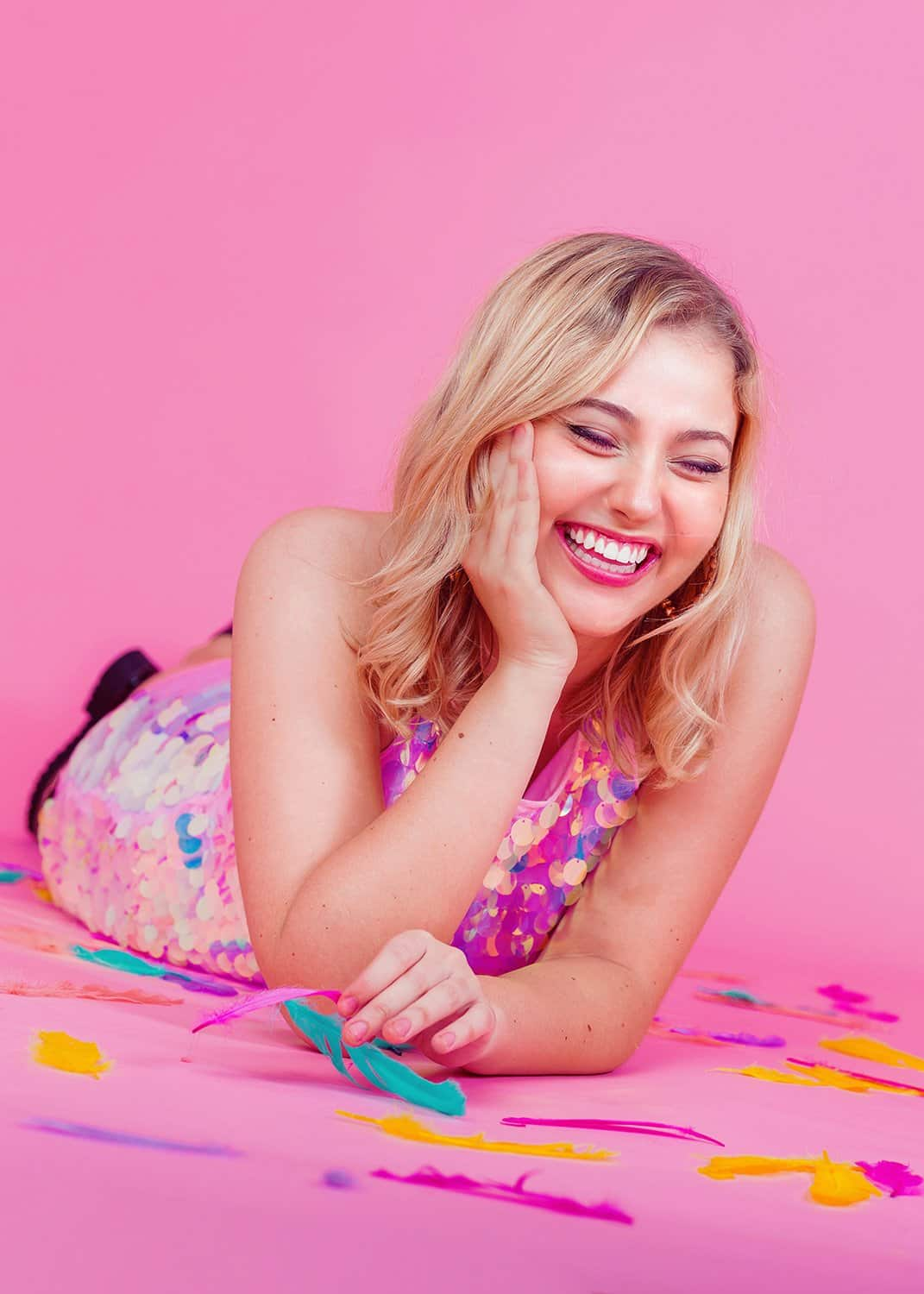 girl laughing on pink backdrop with colorful feathers