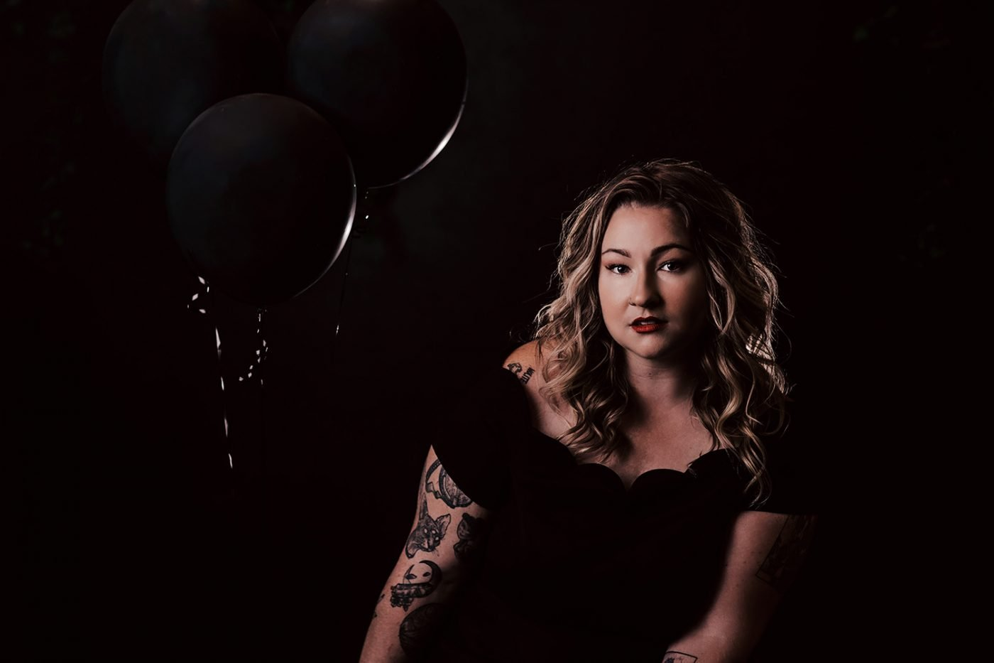 woman with black balloons wearing black dress on black background music video