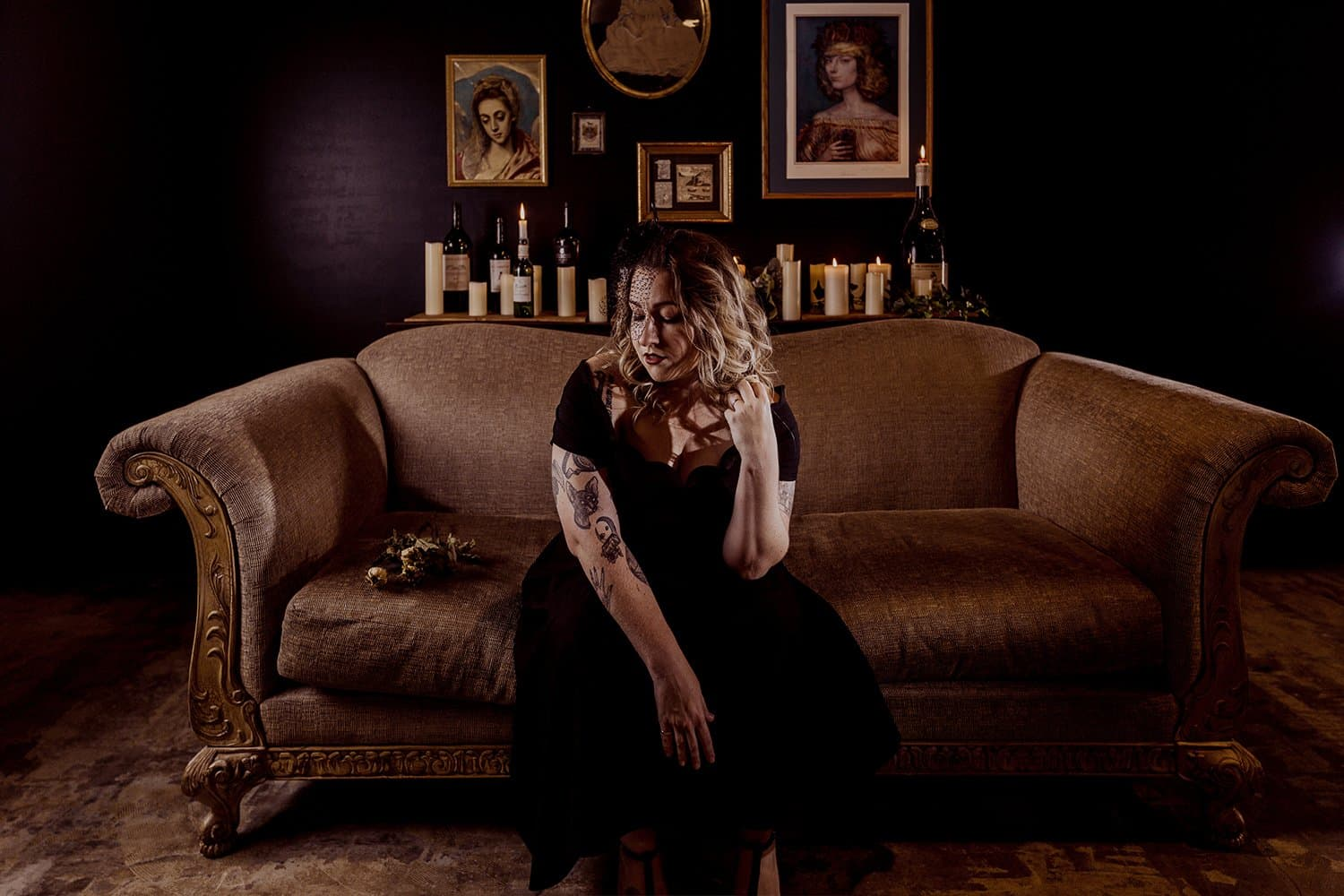 music video woman looking mournful wearing funeral clothes sitting on brown couch with candles