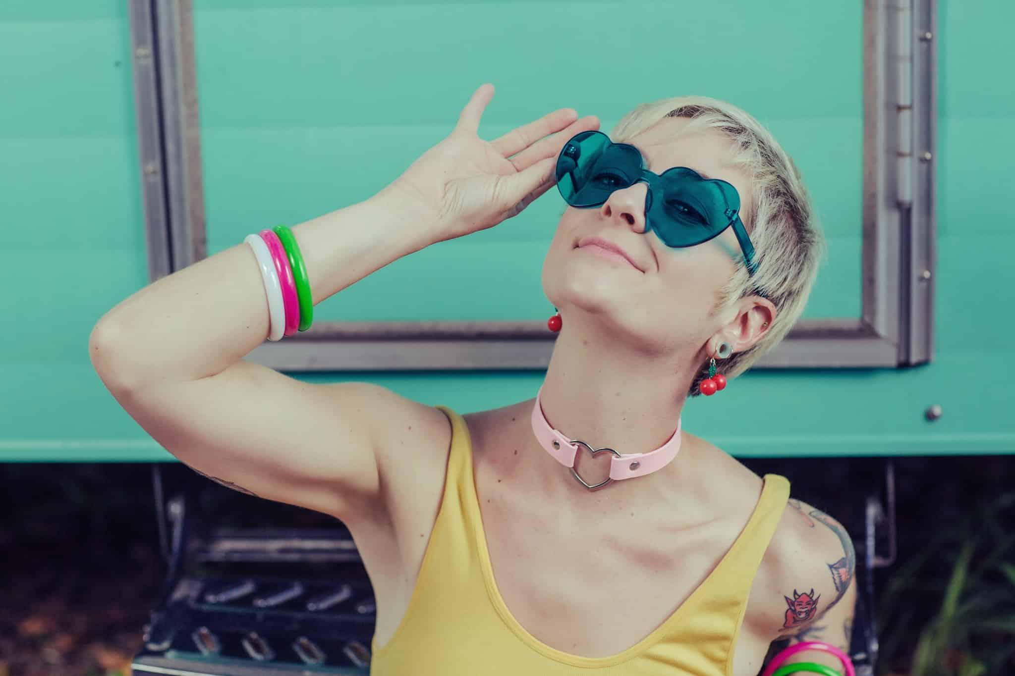 Personal Brand Kate Skales wearing teal heart shaped glasses and pink choker