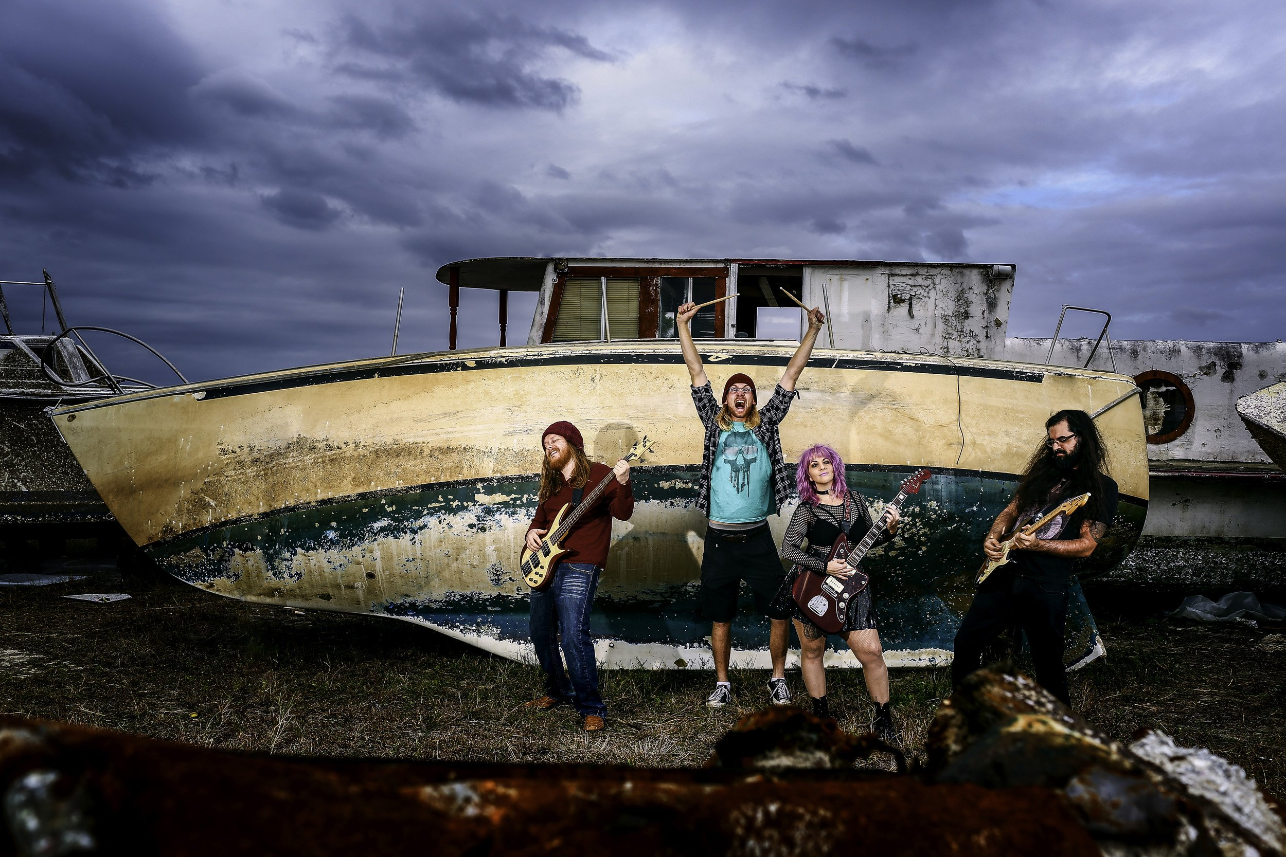 female fronted punk band promo photo in front of decaying boat