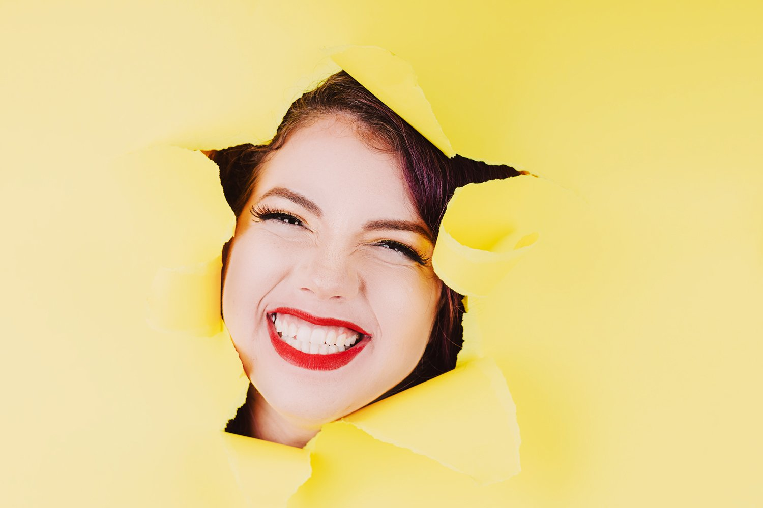 express portraits woman wearing red lipstick smiling through ripped yellow paper