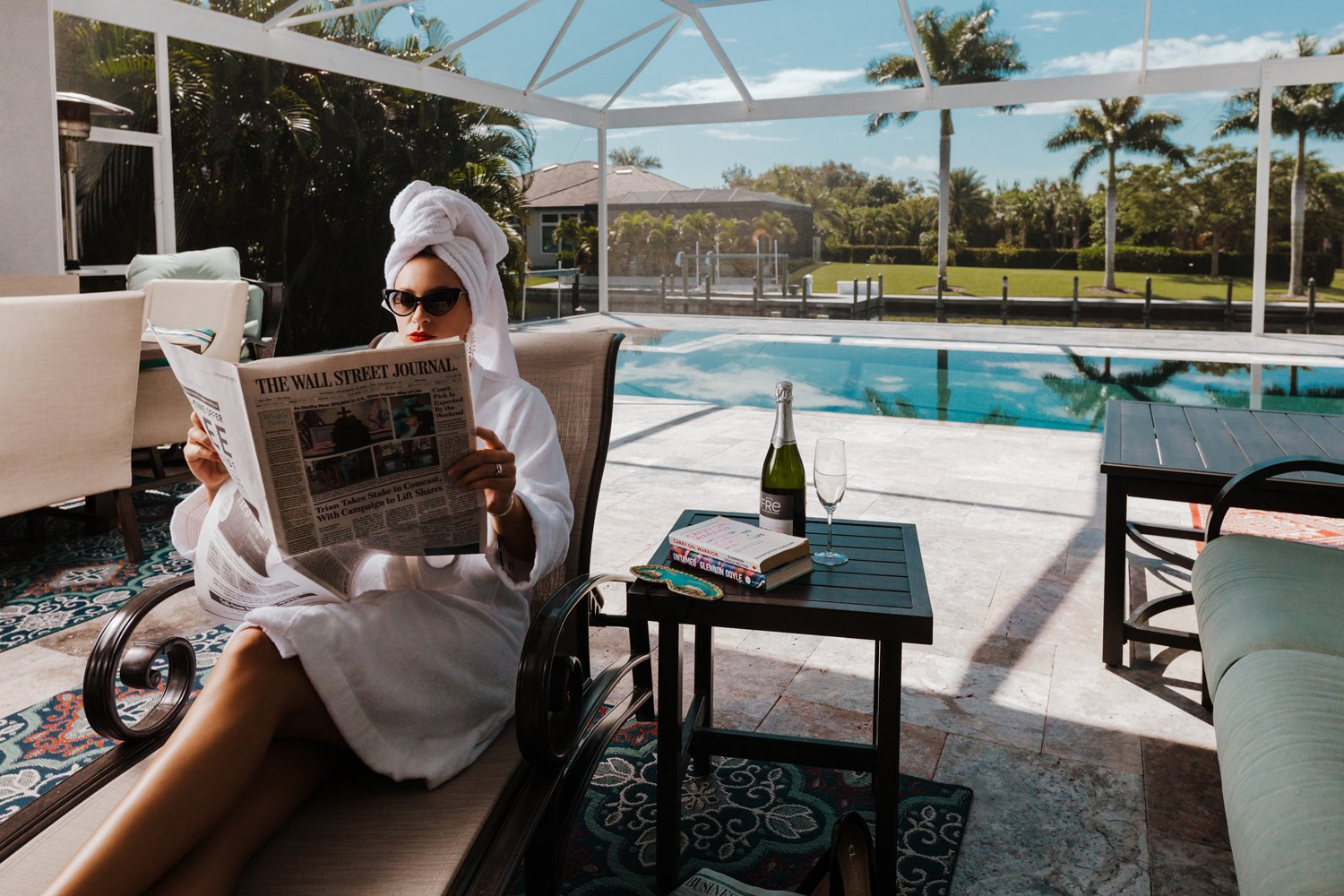 cape coral woman wearing bathrobe reading newspaper by the pool
