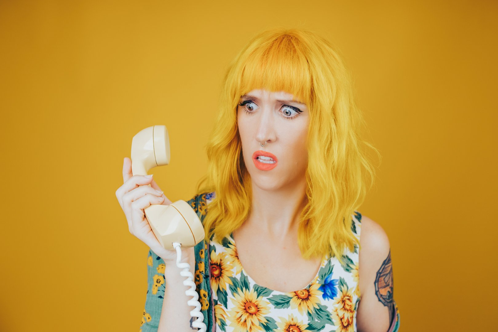 yellow haired woman holding yellow phone on yellow background