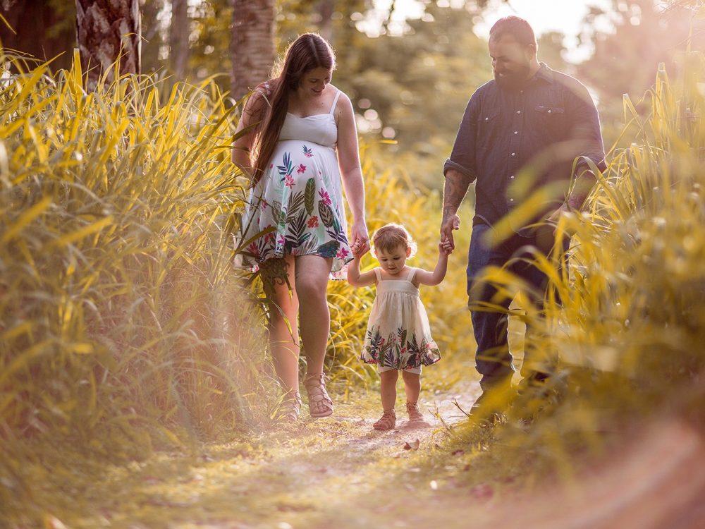 family of three walking through tall grass