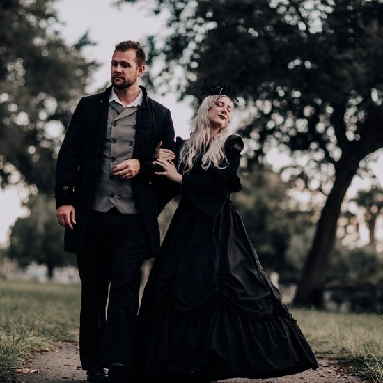 gothic couple walking through florida cemetery