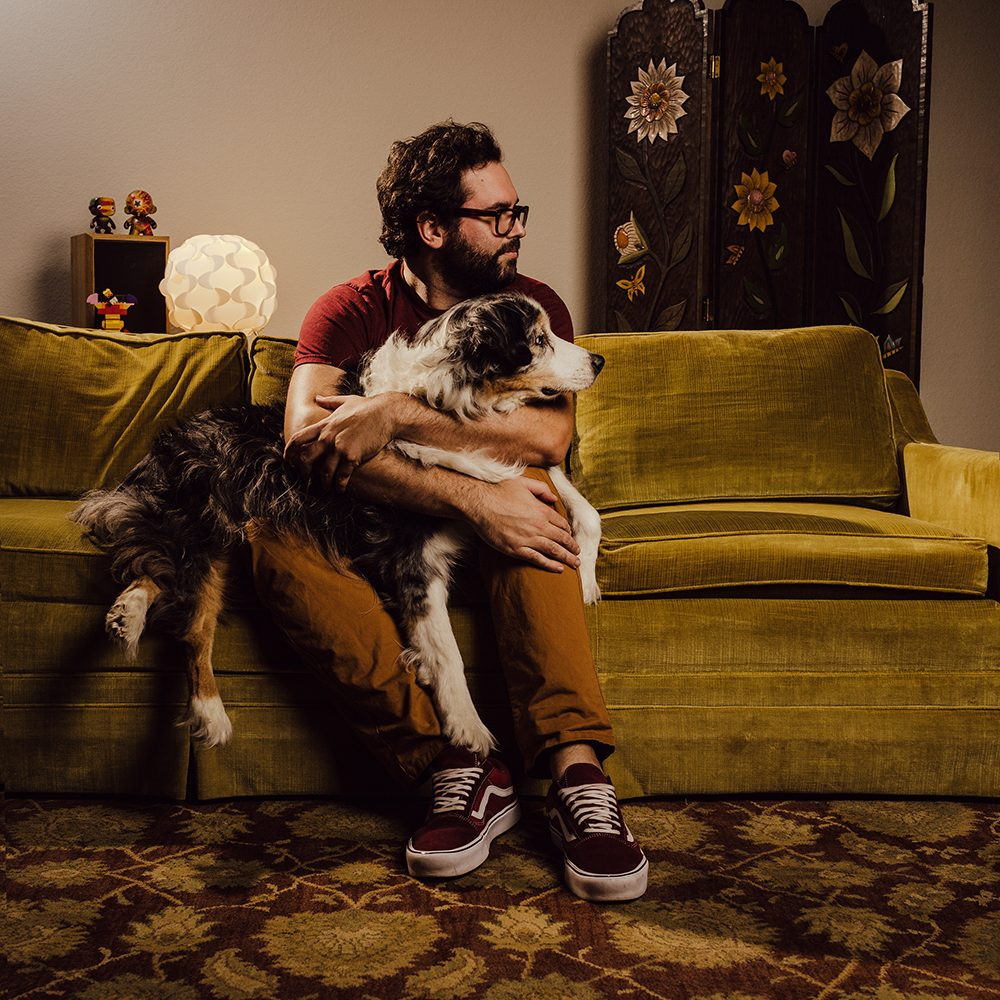 man holding long haired dog in living room portrait photography